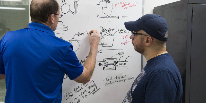Applications engineer draws sketch on whiteboard while machinist looks on